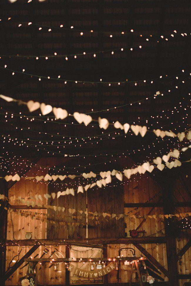 hanging garland in barn for a rustic fall barn wedding reception barn wedding lights