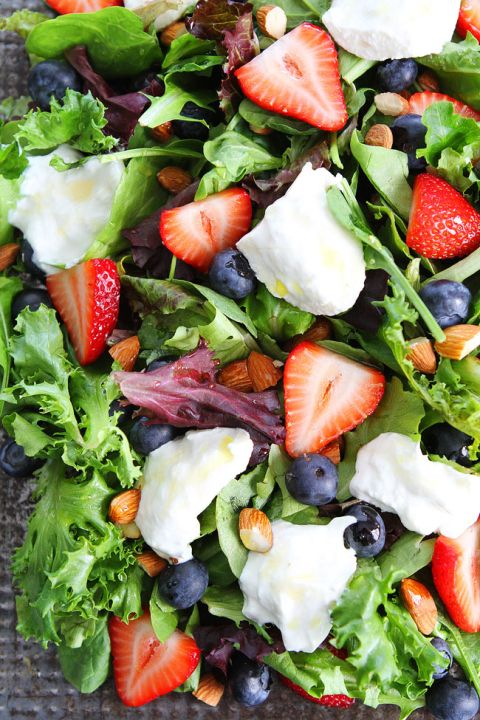 Berry, Burrata, and Almond Salad Recipe on twopeasandtheirpod.com Mixed greens topped with blueberries, strawberries, burrata cheese, almonds, and a simple honey lemon dressing! This easy salad is perfect for the 4th of July!
