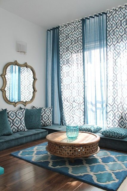 Love the Moroccan style. Low seating cushions instead of couch, beautiful rug, long flowing curtains, and shapely mirror