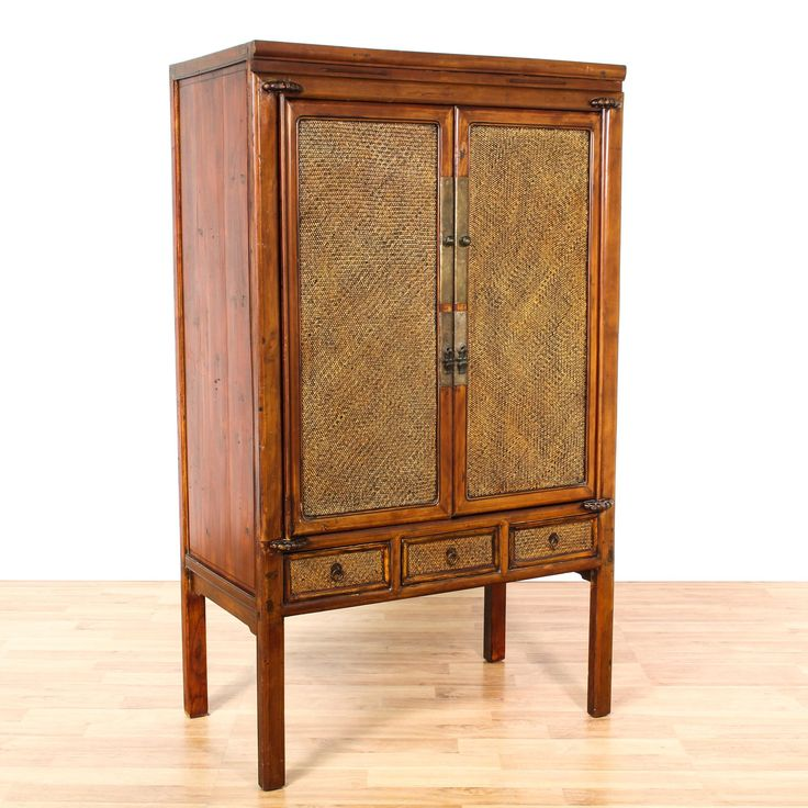 This Chinese wardrobe is featured in a solid wood with a glossy cherry finish. This large armoire has 2 large doors with woven wicker panels, 3 drawers and a large interior cabinet with shelving and drawers. Tropical storage piece perfect for additional closet space! #asian #dressers #armoireorwardrobe #sandiegovintage #vintagefurniture