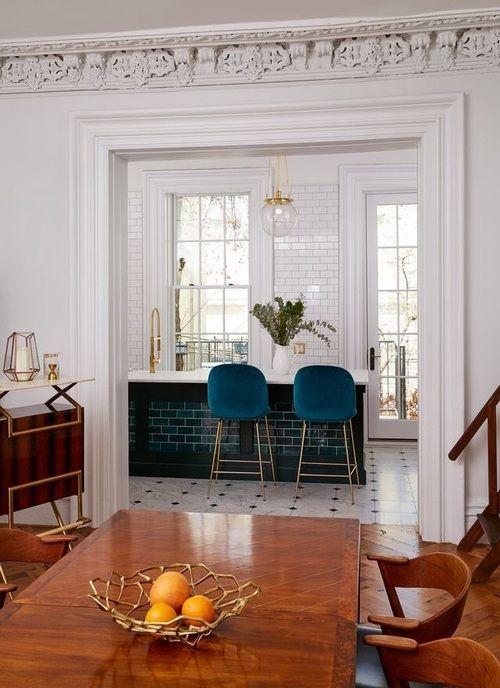 Bold kitchen tiling, ornate mouldings, wood decor, and lush fabrics create a luxurious vibe.
