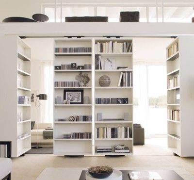 sliding and pivoting bookshelves = flexible open room divider or wall of books. Really nice option for a dual/divided office.