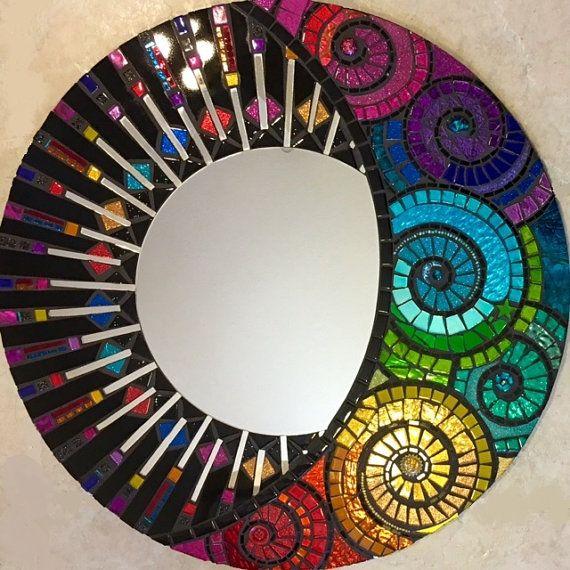 Titulado Brillando a través de... Este es un espejo de mosaico hecho a mano, corte de mano todo por Sol Sister Valerie Watson. Se trata de un total de 24 circular... Con un espejo circular en el centro con el corte a mano alzada Rayos. Esta pieza sería una adición hermosa a cualquier sitio. El diseño es muy colorido. Y necesita ser visto para ser realmente apreciado. Esta obra tiene muchos elementos únicos, incluyendo un montón de resultados Brillo cristal, azulejos, como bien cuentas…