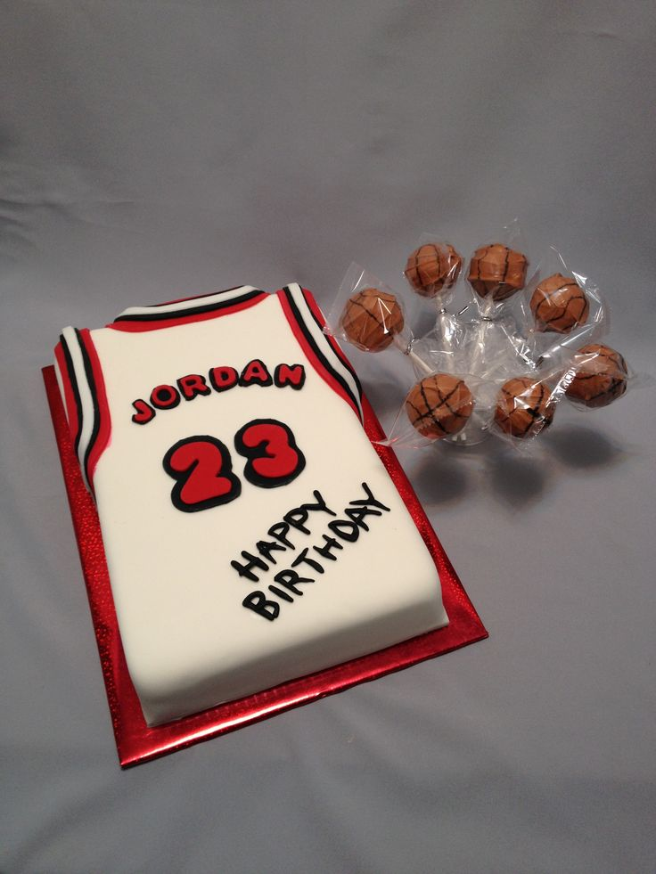 """Basketball Jersey with Basketball Cake Pops - Picture of 1/4 sheet cake made to resemble a basketball jersey.  Cake is a """"made from scratch"""" white cake covered with homemade white marshmallow fondant.  Details were made from Wilton red and black fondant.  Cake pops were made from cake that was carved away from this cake and dipped in a blend of orange and dark cocoa candy melts.  The details on the cake pops were drawn on with an edible candy marker.  Wrapping the cake pops made transporting…"""