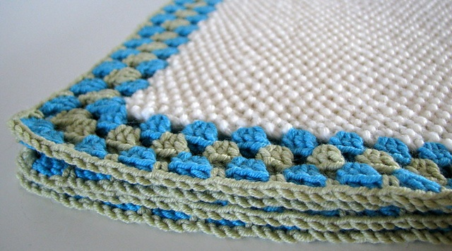 Seed stitch knitted blanket with a granny edging.