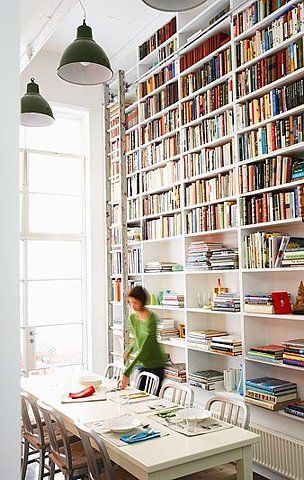 I love books in the dinning room.  This is a great use for a tall wall.  They got a lot of storage in one foot of space.  Light and airy. Book shelves w/ a fancy library ladder. So classy.