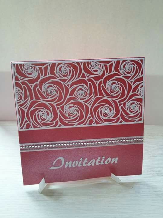Shiny red wedding invitation with cluster rose design in flocking, finished off with silver edged organza ribbon with a row of diamanté