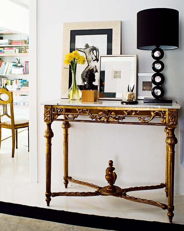 gold console table, black and white lamp. Right mix or vintage glam and modern.