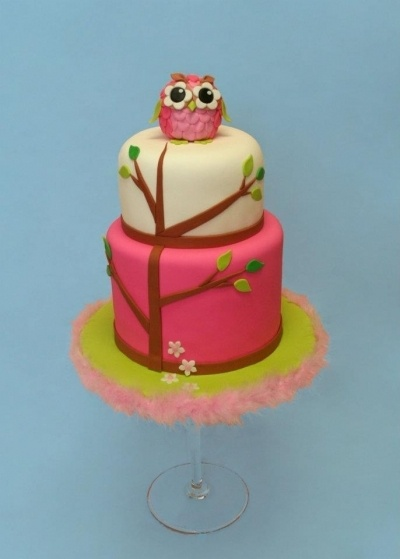 plain white cake with some green and pink stripes or spots and a green ...