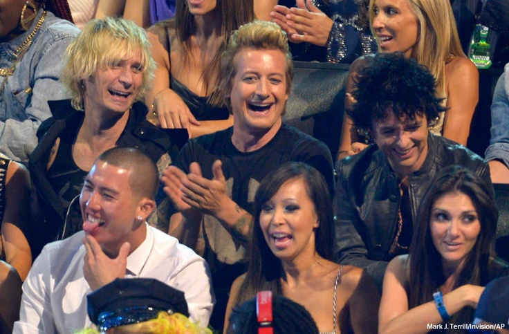 Members of Green Day, from left, Mike Dirnt, Tre Cool and Billie Joe Armstrong sit in the audience at the MTV Video Music Awards