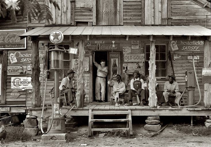 "July 1939. Gordonton, N.C. ""Country store on dirt road. Sunday afternoon. Note kerosene pump on the right and the gasoline pump on the left. Rough, unfinished timber posts have been used as supports for porch roof. Negro men sitting on the porch. Brother of store owner stands in doorway."" 4x5 nitrate negative by Dorothea Lange for the Farm Security Administration."