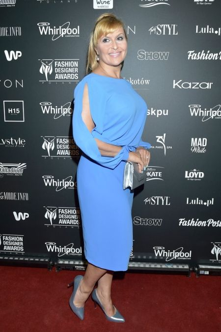 Katarzyna Skrzynecka w błękitnej sukience z rozcięciami i srebrnych szpilkach.