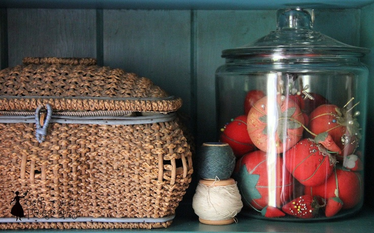 Favorite old sewing basket and a jar of tomato pin cushions.