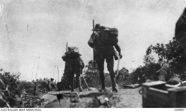 Australian troops going into action across Plugge's Plateau after the landing on 25 April at about midday. Men in front may be seen kneeling in the scrub. The troops were under fire from the other side of Shrapnel Valley. This scene is from a captured Turkish trench overlooking the Anzac Cove beach. Australian War Memorial, G00907.