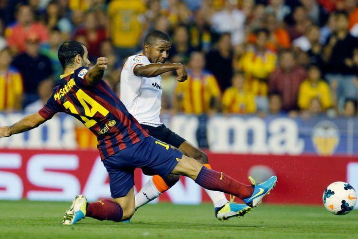 El defensa argentino del FC Barcelona Javier Mascherano intenta evitar el lanzamiento del colombiano Dorlán Pabón, del Valencia CF