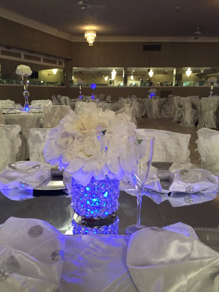 fill glass jar with clear glass stones. put a blue glow stick in the middle. top with white flowers