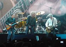 A colour photograph of John Paul Jones, Robert Plant and Jimmy Page performing on stage, with Jason Bonham partially visible on drums in the background  Led Zeppelin