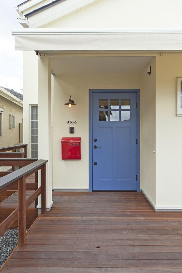 ウッドデッキのアプローチにスカイブルーの玄関ドアが目印 大人