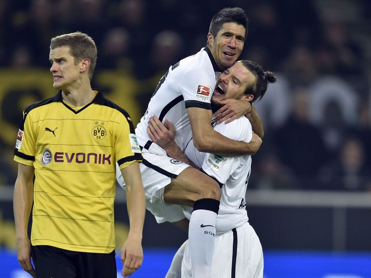 Frankfurt's scorer Alexander Meier, right, celebrates with Slobodan Medojevic, up, next to Dortmund's Sven Bender, left, after scoring the opening goal during the German Bundesliga soccer match in Dortmund, Germany.  Martin Meissner, AP