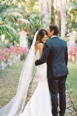 Groom kissing bride in chapel length veil. See more stunning veil trends here: http://www.mywedding.com/articles/9-veils-for-every-type-of-bride/