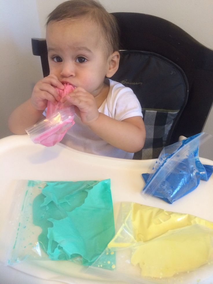 """Mess-free play for One year olds.   Cornstarch, water,  food coloring( i used watercolor paint) and a ziploc bag. Its better to use hands-on with a cookie sheet or bowl but as you can see he would have eaten it right away and the paint is not safe. ( unless your baby has teeth the ziploc bags wont be safe either). Its lots of fun if you teach them to press on it. Also a great activity along the book """" Bartholomew and the Oobleck"""" using green coloring."""