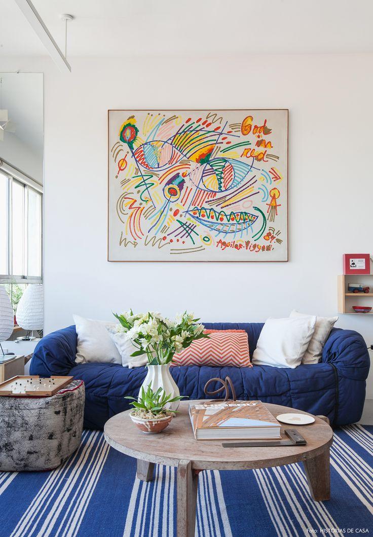 Sala de estar com clima de praia conta com peças em azul, detalhes em vermelho e madeira rústica.