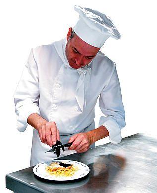 Cocinero con su vestimenta de trabajo, gorro, pañuelo, chaquetilla y delantal de trabajo