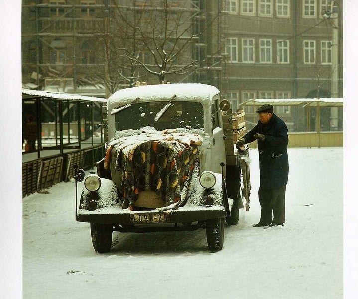 Foto von 1980. Auf dem Domplatz in Erfurt macht ein Markthändler seinen LKW-Oldtimer startklar. Das Auto undefinierter Bauart leistet offenbar noch treue Dienste. Uwe Gerig. - Deutsche Digitale Bibliothek
