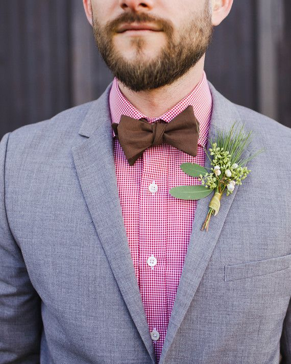 The groomsmen, ushers, fathers, and godfathers adorned their lapels with these boutonnieres of seeded eucalyptus, white berries, and pine at this fall wedding in upstate New York.
