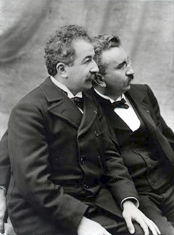 """Auguste and Louis Lumière, inventors, were the first filmmakers in history. They patented the cinematograph, which in contrast to Edison's """"peepshow"""" kinetoscope allowed simultaneous viewing by multiple parties. Their first film, Sortie de l'usine Lumière de Lyon, shot in 1894, is considered the first true motion picture"""