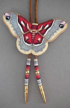 """Beaded Promethea Moth bolo by Todd Lonedog Bordeaux, Lakota  The subtle colors in Mr. Bordeaux's Promethea moth are truly enchanting. Leather backing; suede bolo cord with brass tips  4 1/2"""" x 3""""; 35"""" cord  AOI00075 This is a special order item. For pricing and availability, please call 207 967-2122 or send us an email: admin@homeandaway.biz."""