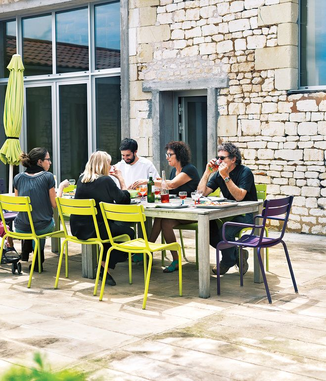 For a stone farmhouse in Paris, cerebral architect Matali Crasset paired a custom-made table with Fermob's Luxembourg chairs for alfresco meals on the patio. Photo by Jonas Ingerstedt.