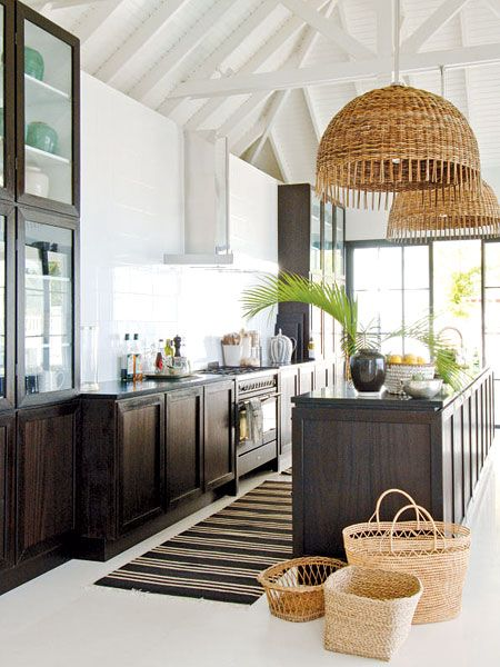 Wicker isn't just for chairs – these statement-making Italian lamps add coastal style in a creative way. To keep the black mahogany cabinets from looking too dark, the interiors were painted white, and glass fronts were added to reflect natural light. (Photo: Jean Philippe-Piter)