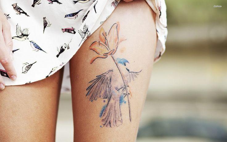 chica nos enseña su tatuaje en la parte superior del muslo de un colibri y ina amapola