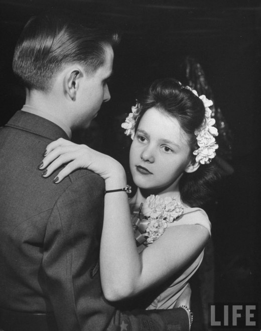 Young girl with flowers in her hair, Southwest High School Kansas City ROTC Ball, LIFE magazine, 1945. Photo by Myron Davis. Look at that baby face!