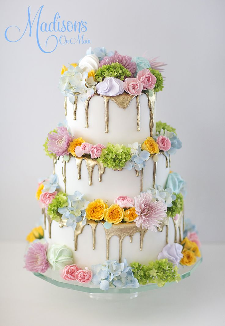 Pastel wedding cake.  Fondant with a gold painted ganache drip.  Pastel fresh flower and meringues!