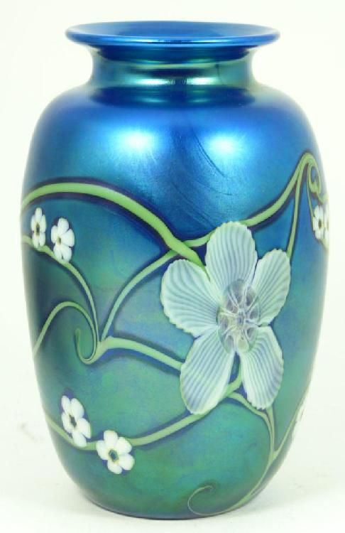 """Orient & Flume iridescent art glass vase having a floral design over cobalt ground. Bottom holds etched company marks and dated 1984. Also artist signed to bottom. Has original label to bottom. Measures 5 3/4"""" height (14.6cm). Total weight of 449 gra [...more]   Starting Bid: USD 100 Elite Decorative Arts  Click image for more info"""