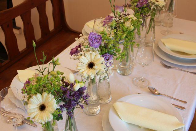 Slavnostní svatební tabule ve fialovo-bílé kombinaci vyzdobená květy gerber, eustomy, kontryhelu, fresiemi, staticí a nevěstiným závojem.