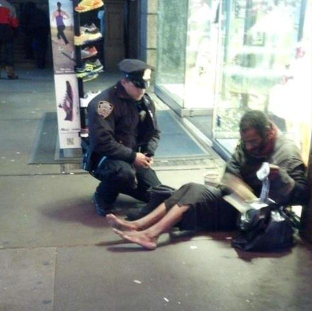NYPD officer Lawrence DePrimo gives a pair of boots to a barefoot man in Manhattan.
