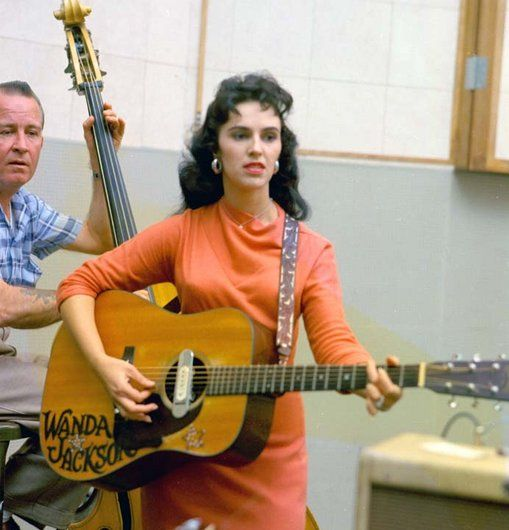 """Wanda Jackson, born 1937, still the Queen of Rockabilly, still playing today. Seen here with bass player Skeets McDonald. Link goes to her own website. Try this 1961 video clip of """"Stupid Cupid"""", via @tzipporah26 : https://www.youtube.com/watch?v=9oaT8i5L2a0  -or- """"Hard-Headed Woman"""" at https://www.pinterest.com/pin/293437731941262626/"""