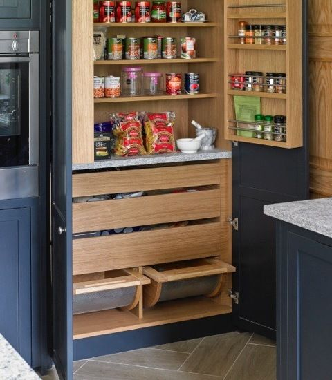 Blue grey Esher kitchen pantry cabinet interior in light wood.