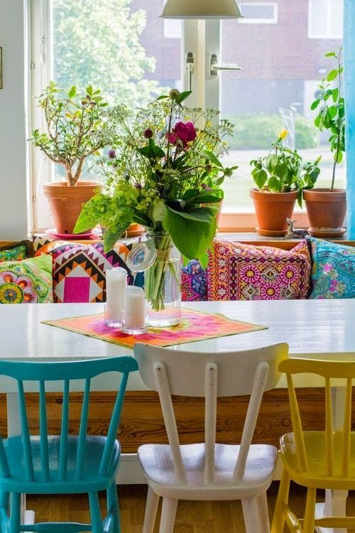Colourful Bohemian Dining Room With Painted Chairs Mix And Match Colourful Fabric Pillows And House Plants