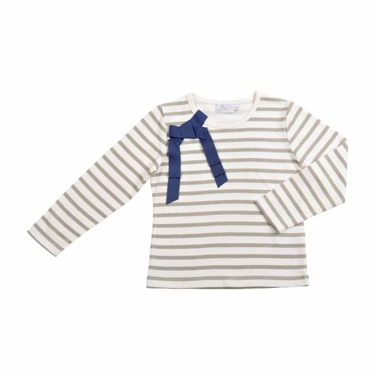 Franela de algodón para niña con diseño de rayas color hueso y verde olivo. Detalle, a un lado del cuello de un lazo hecho en cinta de gros en color azul marino.