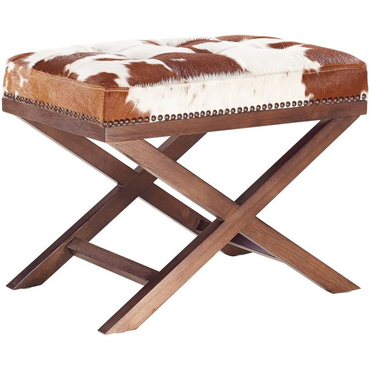 - Info - Features - Dimensions Add some rustic elegance to your living room or entryway with the Vache Cowhide Ottoman. Featuring genuine cowhide upholstery, bronze nail head trim, and solid oak legs.