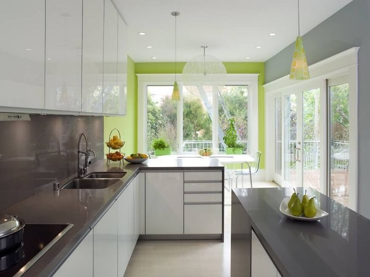 A bright modern kitchen with minimalist white cabinets and light gray countertops and backsplash. An attached dining area to the rear of the space is painted in a rich spring green, which is carried into the more neutral kitchen via the pendant lights and a display dish of pears.