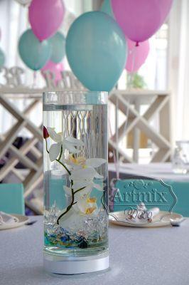 Цилиндрическая прозрачная ваза с одиночно вертикально стоящими орхидеями