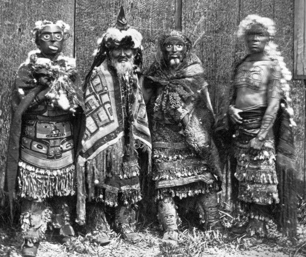 Men in ceremonial regalia. Two men (left, third from left) wear a mask. Masset, 1881. Photo by Edward Dossetter; courtesy of the Royal BC Museum, BC Archives, B-03590.