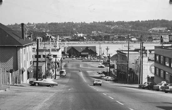 Photograph shows a street view of Eighth Street, looking toward the river, showing the intersections of 8th and Victoria, Carnarvon, Columbia, and Front streets. Shows edge of CPR station, The Old Spaghetti Factory on the right, and a full view of The King Neptune restaurant at the foot of the street. [1980?] IHP7636