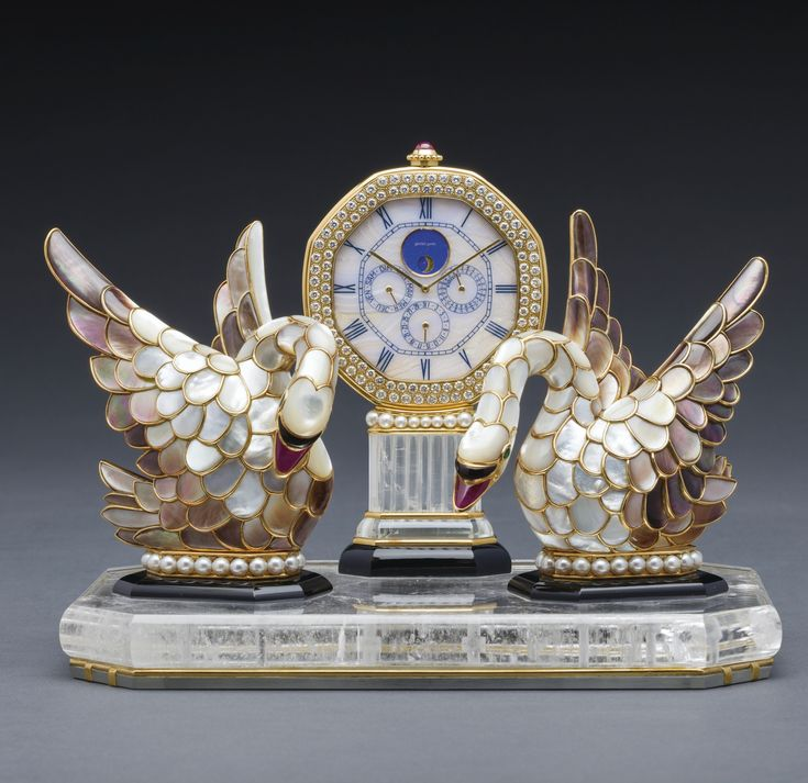 GERALD GENTA SWAN LAKE A FINE AND VERY RARE GOLD, MULTI-COLOURED MOTHER-OF-PEARL, DIAMOND, RUBY, EMERALD, TOURMALINE, ONYX AND ROCK CRYSTAL PERPETUAL CALENDAR CLOCK WITH PHASES OF THE MOON CIRCA 1990. sotheby's hk0476lot6pbllde