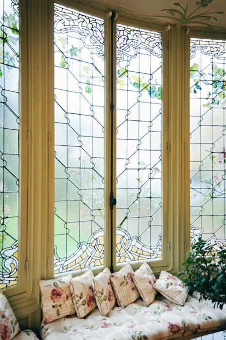 The high leaded glass windows make this large window seat even more elegant and lovely. The green leaf designs are even carried into the ceiling!